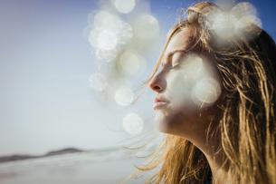 Serene woman basking in sunshine on beachの写真素材 [FYI04323989]