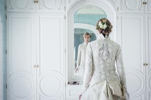 Elegant bride in lace wedding dress at mirrorの写真素材 [FYI04323991]