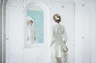 Elegant bride in lace wedding dress at mirrorの写真素材 [FYI04323992]