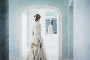 Elegant bride in lace wedding dress at mirrorの写真素材 [FYI04323993]
