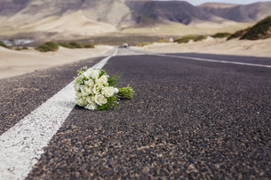 Bridal bouquet with roses laying on remote roadの写真素材 [FYI04323996]
