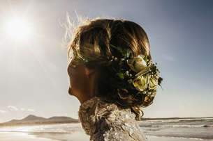 Bride with flowers in hair on sunny ocean beachの写真素材 [FYI04323998]