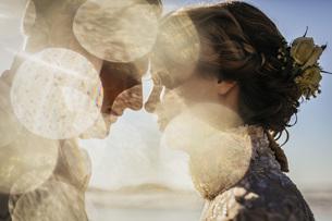 Golden light illuminating profile of bride and groomの写真素材 [FYI04323999]