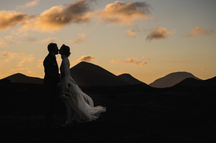 Silhouette bride and groom kissing at dusk with tranquil mountains in backgroundの写真素材 [FYI04324001]
