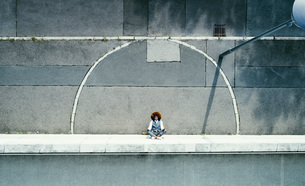 View from above young man meditating on urban sidewalkの写真素材 [FYI04324004]