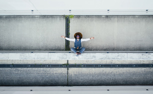 View from above portrait exuberant young man on urban ledgeの写真素材 [FYI04324005]