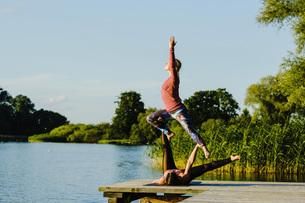 Women practicing acroyoga on sunny lakeside dockの写真素材 [FYI04324011]