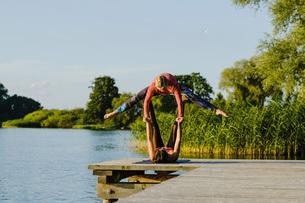 Women practicing acro yoga on sunny lakeside dockの写真素材 [FYI04324012]
