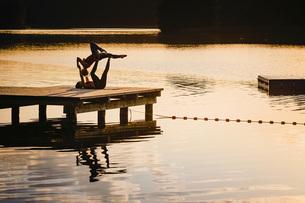 Women practicing acro yoga on lakeside dock at duskの写真素材 [FYI04324014]
