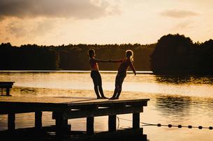 Women practicing acro yoga on tranquil sunset lake dockの写真素材 [FYI04324015]