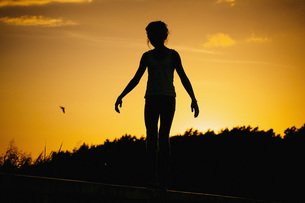Silhouette woman standing against sunset skyの写真素材 [FYI04324018]
