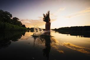 Carefree girl jumping into lake at sunset, Barnin, Mecklenburg-Vorpommern, Germanyの写真素材 [FYI04324021]