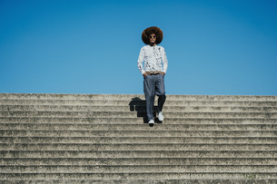 Portrait confident, cool young man with afro on sunny stepsの写真素材 [FYI04324023]