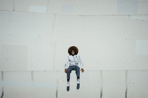 Portrait happy young man with afro sitting on wallの写真素材 [FYI04324024]