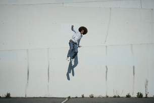 Portrait carefree young man with afro jumping at sunny wallの写真素材 [FYI04324026]