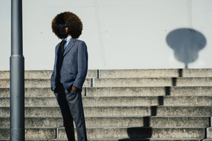 Portrait cool, well dressed young man with afro at urban stepsの写真素材 [FYI04324029]