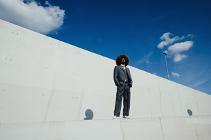 Portrait confident, cool, well-dressed young man with afro standing on urban wallの写真素材 [FYI04324030]