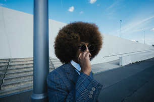 Well-dressed young man with afro smoking cigarette on urban sidewalkの写真素材 [FYI04324031]