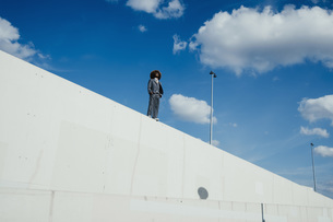 Cool, well-dressed young man with afro standing on sunny urban wallの写真素材 [FYI04324034]
