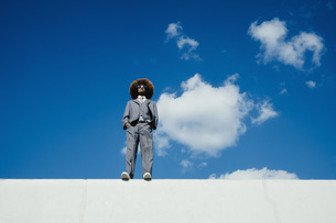 Confident, cool, well-dressed young man with afro standing on sunny wall against blue skyの写真素材 [FYI04324035]