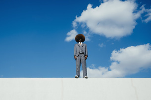 Portrait confident, cool, well-dressed young man with afro standing on wall against skyの写真素材 [FYI04324036]