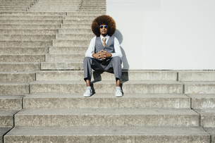 Portrait confident, cool, well-dressed young man with afro sitting on urban stepsの写真素材 [FYI04324037]