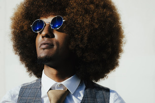 Portrait confident, cool, well-dressed young man with afro looking awayの写真素材 [FYI04324038]