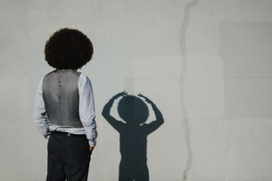 Young man with afro watching gesturing shadow on sunny wallの写真素材 [FYI04324039]