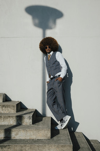 Portrait confident, cool, well-dressed young man with afro on urban stepsの写真素材 [FYI04324040]