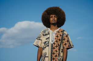 Portrait confident young man with afro standing against blue sky with cloudsの写真素材 [FYI04324041]
