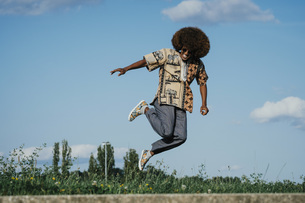Carefree young man with afro jumping for joyの写真素材 [FYI04324042]