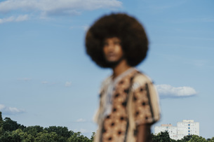 Defocused portrait young man with afro standing against sunny blue skyの写真素材 [FYI04324045]