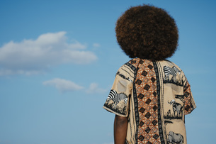 Young man with afro looking up at clouds in blue skyの写真素材 [FYI04324046]