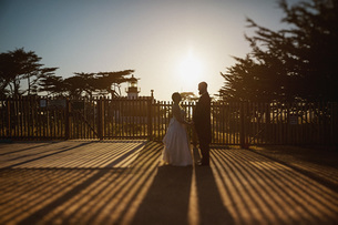 Bride and groom standing outside sunny lighthouse, Monterey, Lucas Point, California, USAの写真素材 [FYI04324049]