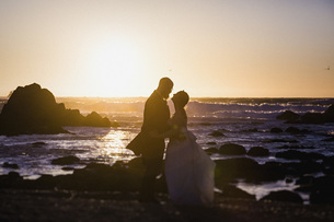 Silhouette bride and groom on tranquil sunset ocean beach, Monterey, Lucas Point, California, USAの写真素材 [FYI04324050]