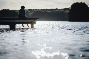 Woman relaxing at the edge of sunny lake dockの写真素材 [FYI04324051]