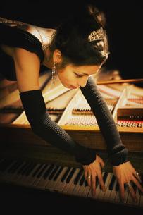 Elegant pianist in tiara leaning over pianoの写真素材 [FYI04324054]