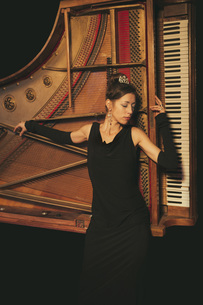 Elegant, well-dressed woman laying on pianoの写真素材 [FYI04324057]