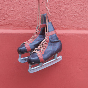 Ice skates hanging against red wallの写真素材 [FYI04324066]