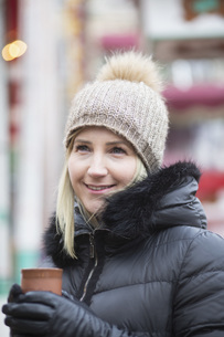 Portrait smiling woman in warm clothing drinking teaの写真素材 [FYI04324067]