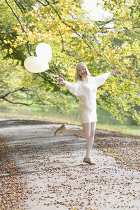 Carefree woman with balloons in autumn parkの写真素材 [FYI04324068]
