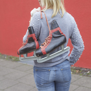 Woman carrying ice skates over shoulderの写真素材 [FYI04324072]
