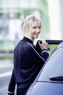 Portrait confident woman getting into carの写真素材 [FYI04324074]