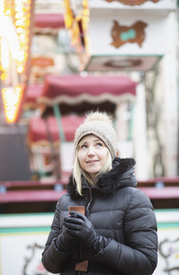 Woman in warm clothing drinking tea at carnivalの写真素材 [FYI04324075]