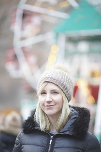 Portrait confident woman in warm clothing at carnivalの写真素材 [FYI04324076]