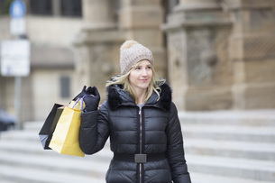 Woman in warm clothing carrying shopping bagsの写真素材 [FYI04324077]