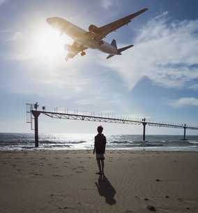 Boy looking up at airplane flying low over ocean near Lanzarote Airport, Puerto del Carmen, Spainの写真素材 [FYI04324078]