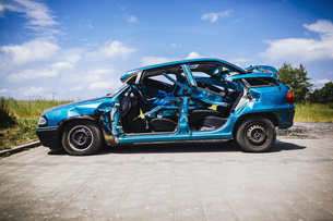 Mangled blue car in sunny parking lotの写真素材 [FYI04324091]