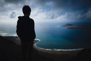 Boy looking at scenic ocean bay view with storm clouds overhead, Lanzarote, Canary Islands, Spainの写真素材 [FYI04324094]