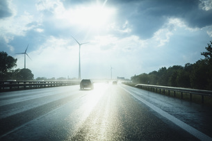 Sun reflecting on wet Autobahn Berliner Ring with wind turbines in distance, Berlin, Germanyの写真素材 [FYI04324095]